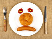 Sausage with bun on the plate as sad Face — Stock Photo