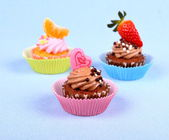 Three appetizing cupcakes with heart, tangerine, and strawberry — Stock Photo