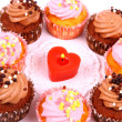 Chocolate and pink cup cakes with candle heart, top view — Stock Photo #40316421