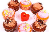 Chocolate and pink cup cakes with candle heart, top view — Stock Photo