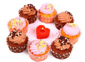 Chocolate and pink cup cakes with candle heart — Stock Photo
