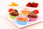 Four appetizing cupcakes on white plate — Stock Photo