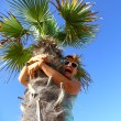 Mature woman sits on palm tree, scared — Stock Photo #40556345