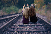 Two girls sitting on railway tracks and show love — Stock Photo
