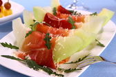 Ripe melon with ham, parmesan on white plate, cheese — Stock Photo