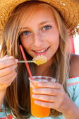 Beautiful girl with an iced drink, straw hat on beach — Stock Photo