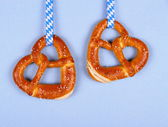 Two pretzel in heart shape on blue background — Stock Photo