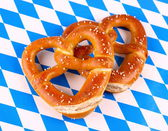 Two pretzel in heart shape on white blue background — Stock Photo