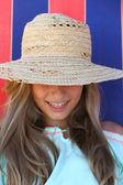 Smiling teen girl in hat on beach — Stok fotoğraf