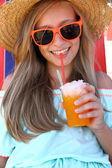 Beautiful girl in sunglasses and slush on beach — Stock Photo