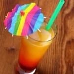 Red, yellow cocktail with lemon, straw, umbrella deco — Stock Photo #45539475