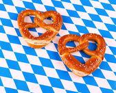 Two pretzel in heart shape on white blue background — Stock Photo