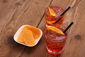 Spritz aperitif - two orange cocktail, ice cubes, potato chips — Stock Photo