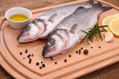 Two fresh sea bass fish on cutting board with ingredients — Stock Photo