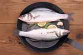 Two fresh moronidae fish on frying pan with ingredient — Stock Photo