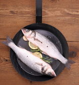 Two fresh sea bass fish on frying pan with ingredients — Stock Photo