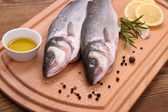 Two fresh sea bass fish on cutting board — Stock Photo