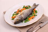 Grilled whole sea bass with vegetables and lemon — Stock Photo