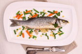 Fried whole sea bass with vegetables and lemon — Stock Photo