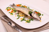 Fried whole sea bass with vegetables, lemon — Stock Photo