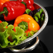 Freshly washed fresh vegetables in a metal colander isolated over black background. - Stock Photo