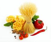 Włoski makaron z pomidorami, papryką i bazylia na białym tle. — Zdjęcie stockowe