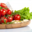 Fresh cherry tomatoes and salad in a wooden plate — Stock Photo