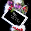 Tablet PC with Christmas decoration on black — Stock Photo
