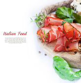 Prosciutto with salami, cheese and basil — Stock Photo
