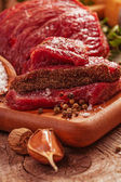 Raw meat on board with herbs — Stock Photo