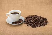 Tasty Coffee with coffee beans on background — Stock Photo