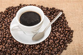Tasty Coffee with coffee beans on background — Stockfoto