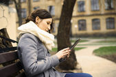 Young woman sitting with Tablet and reading — Stock Photo
