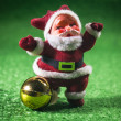 Santa Claus with gold ball on green background. — Stock fotografie #36039933