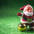 Santa Claus with gold ball on green background. — Stock Photo