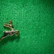 Stock Photo: Golden raindeer jumping on green carpet.