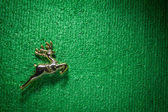 Golden raindeer jumping on green carpet. — Stock Photo