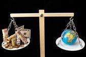 Aarde en geld op een twee pan evenwicht — Stockfoto