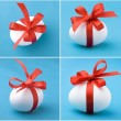 White egg wrapped around with red ribbon over blue background — Stock Photo