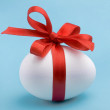 White egg wrapped around with red ribbon over blue background — 图库照片