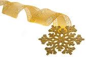 Gyllene band curl med snöflinga på vit — Stockfoto