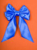 Blå satin rosett på orange sammet bakgrund — Stockfoto