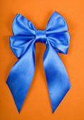 Blue satin bow on yellow velvet background — Stock Photo