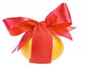 Pisanka pomarańczowy owinięty wokół z czerwoną wstążką łuku na białym tle — Zdjęcie stockowe