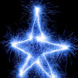 Christmas star made by sparkler on a black background — Stock Photo