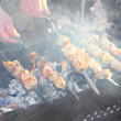 Man hands grilling tasty barbecue on black coals on mangal outdoor — Stock Photo #13991802