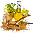 Stock Photo: Mustard oil jar and powder, seeds, spoon and mustard flower blossom on white