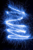 Blue sparkler on dark background — Stock Photo