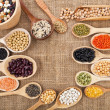 Various food ingredients: beans, legumes, peas, lentils in wooden spoon on the sackcloth background — Photo