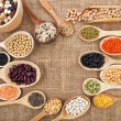 Various food ingredients: beans, legumes, peas, lentils in wooden spoon on the sackcloth background - Stock Photo